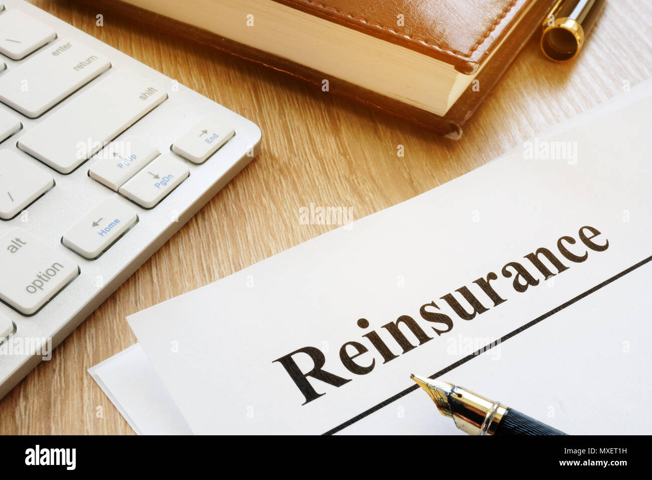 Documents with title reinsurance on a desk. - Stock Image