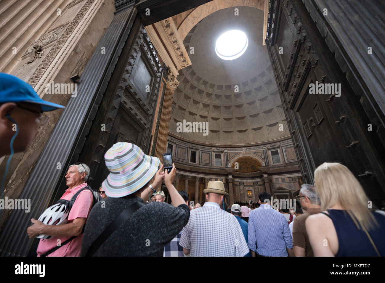 Rome Pantheon interior, light true the hole on dome, tourists visiting - Stock Image