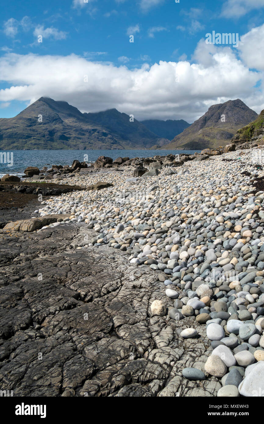 Pebbles and rocks of Glen Scaladal Bay (Cladach a Ghlinne) near Elgol, with sea and Black Cuillin Mountains beyond, Isle of Skye, Scotland, UK - Stock Image