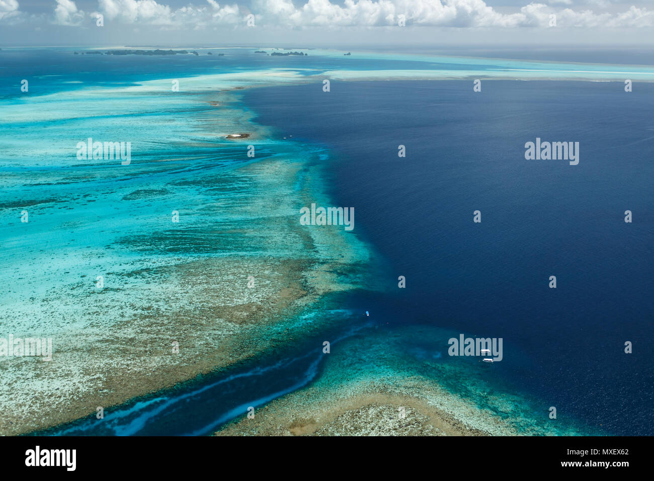 Colorful aerial view of large sweep of coral reefs and  tiny white sandbar islands with large tour boats traveling nearby - Stock Image