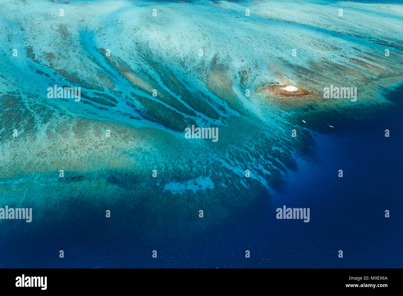 Colorful aerial view of large coral reef surrounding tiny white sandbar island with two boats approaching - Stock Image
