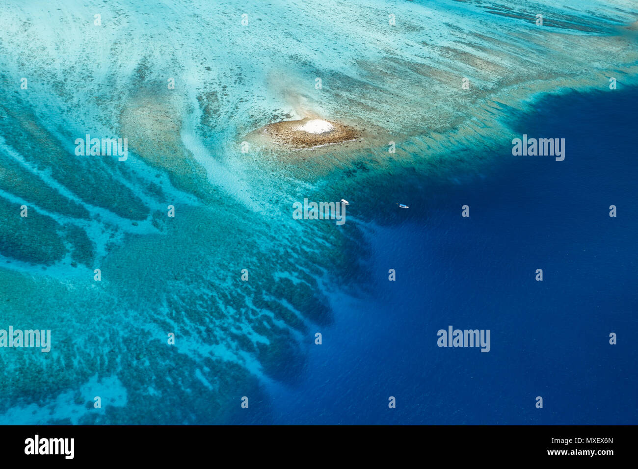 Colorful aerial view of large coral reef surrounding tiny white sandbar island with boats approaching - Stock Image