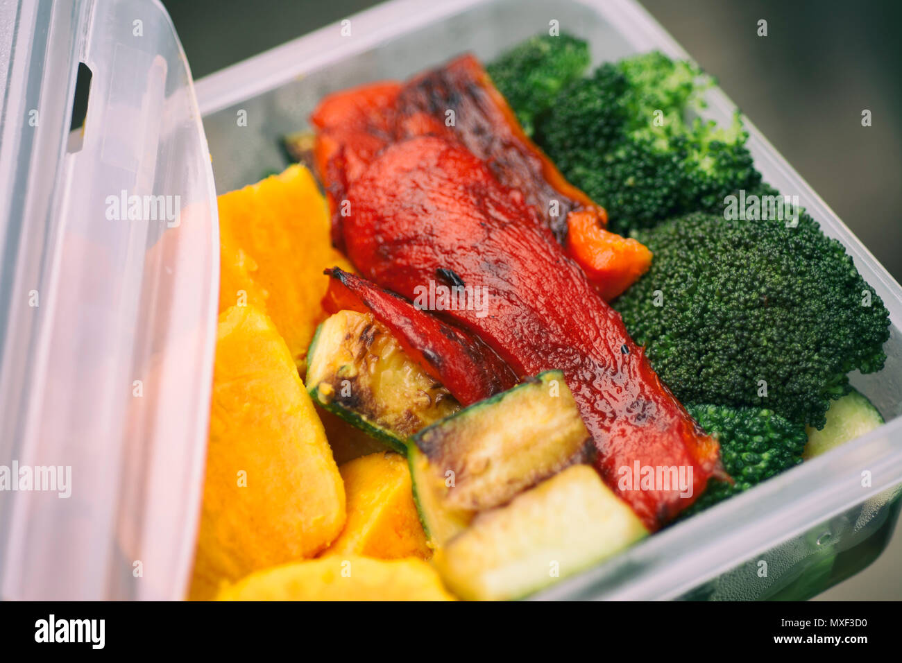 Packed Lunch, Roasted Vegetables Red Bell Pepper Broccoli Sweet Potato Zucchini in Tupperware - Stock Image