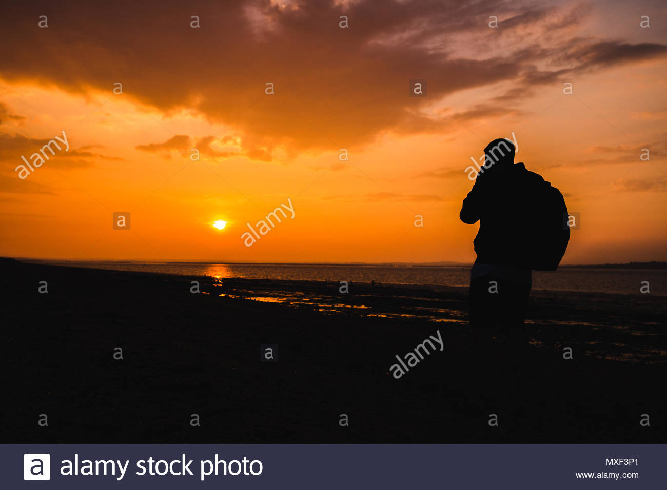 Taking a photo of the sunset - Stock Image