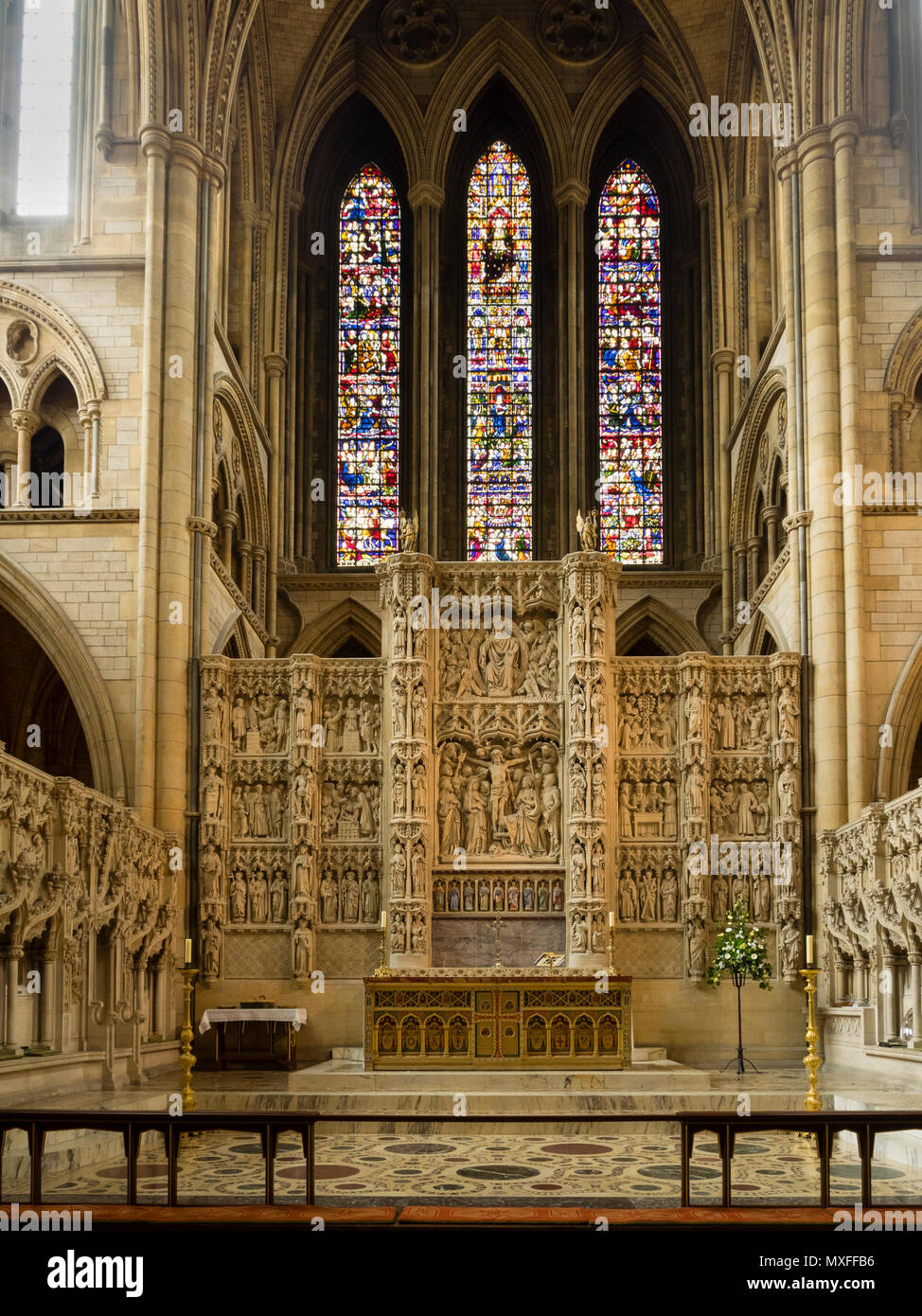 Altar and intricately carved reredos below the stained glass window of the Victorian Truro Cathedral, Cornwall, UK - Stock Image