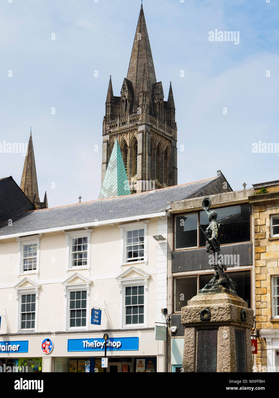 The main and secondary spires of Truro Cathedral dominate the skyline above the war memorial in Boscowan street, Truro, Cornwall, UK - Stock Image