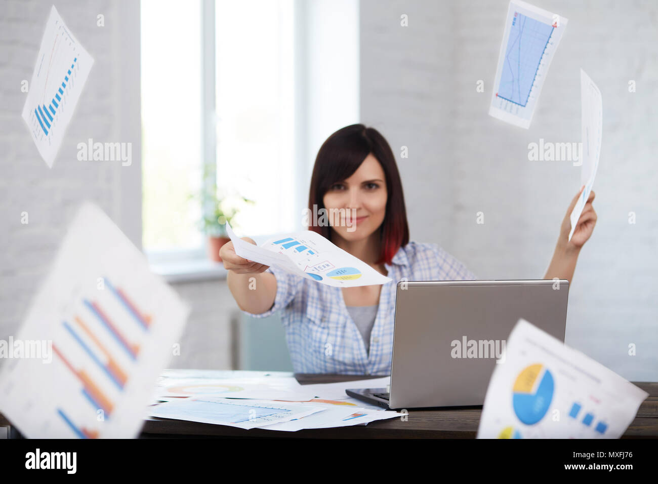 Happy and smiling female worker throws documents in office with falling papers around.Finishing work in time.Time management, deadline concept. - Stock Image