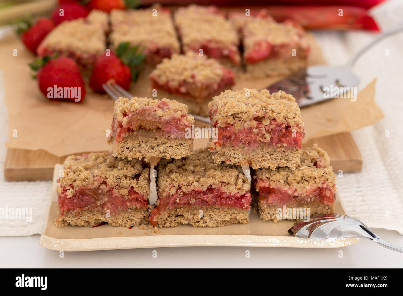 A healthy snack or dessert. Strawberry and rhubarb crumble bars stacked on a handmade ceramic plate, with a silver spoon. - Stock Image