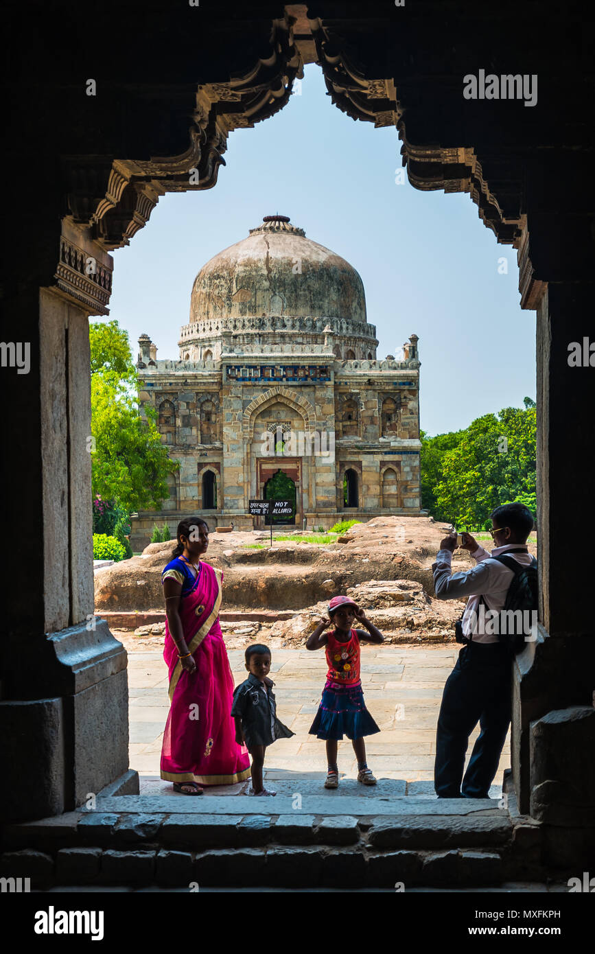 An Indian family on a trip, photographing themselves on the background of a Hindu temple. India, Delhi June 2015 - Stock Image