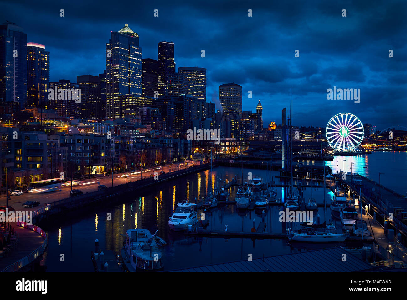 Seattle Waterfront, Big Wheel  Downtown Seattle skyline at dusk. The ferris wheel stands out along the shoreline. Washington State, USA. - Stock Image