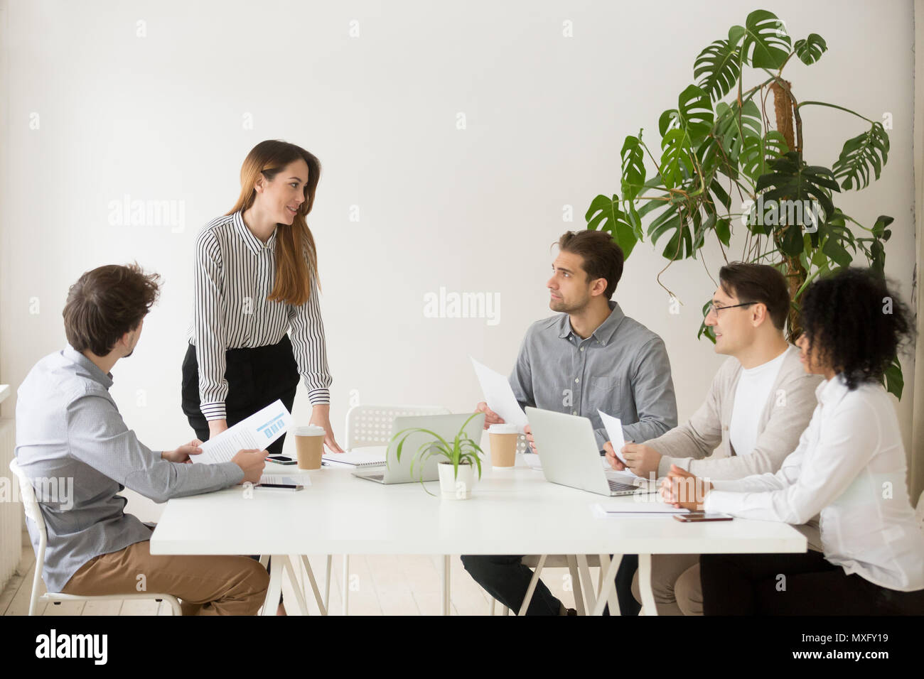 Female business coach making presentation to workers - Stock Image