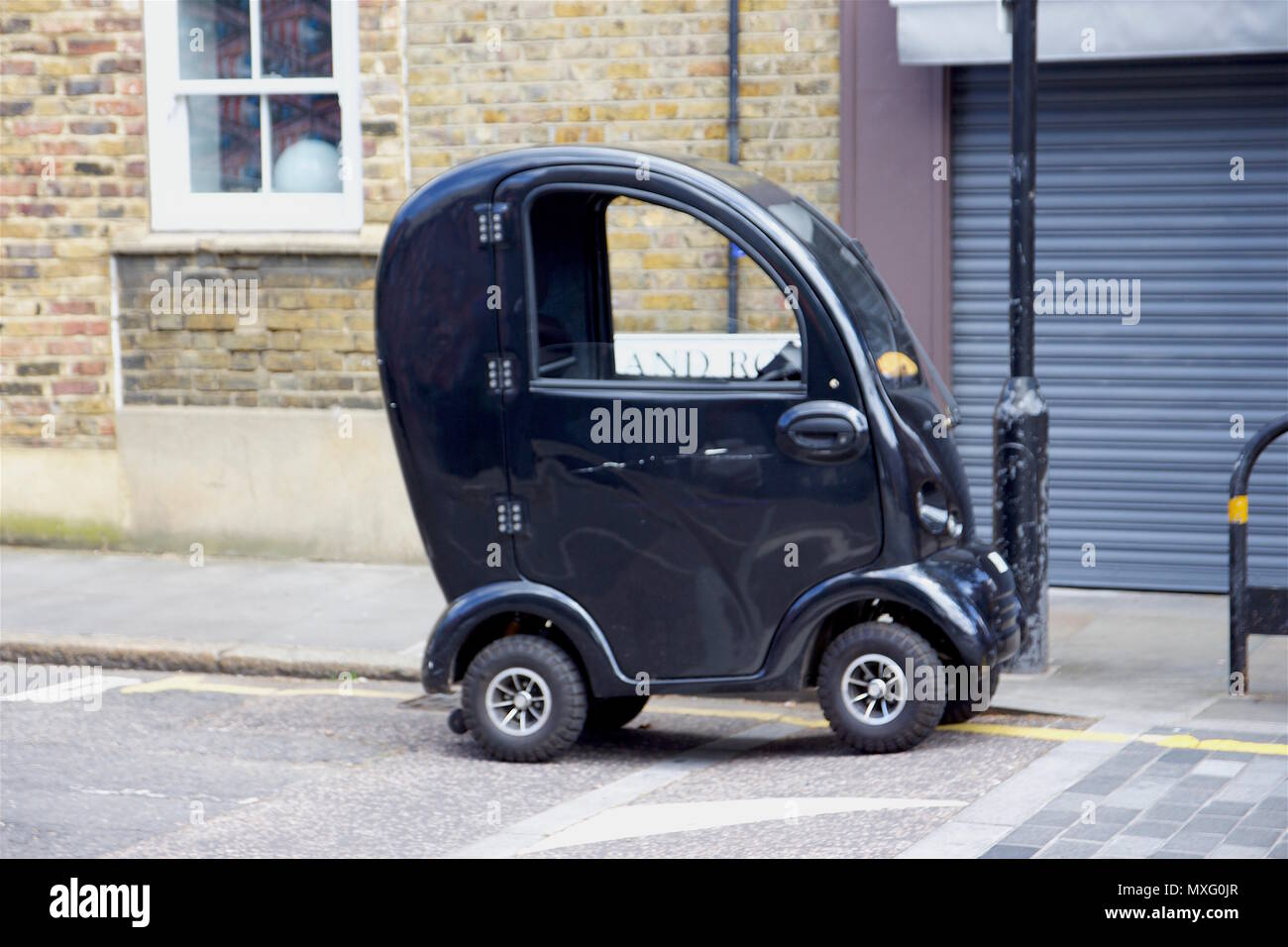 A parked, black one passenger car in Bow, East London - Stock Image