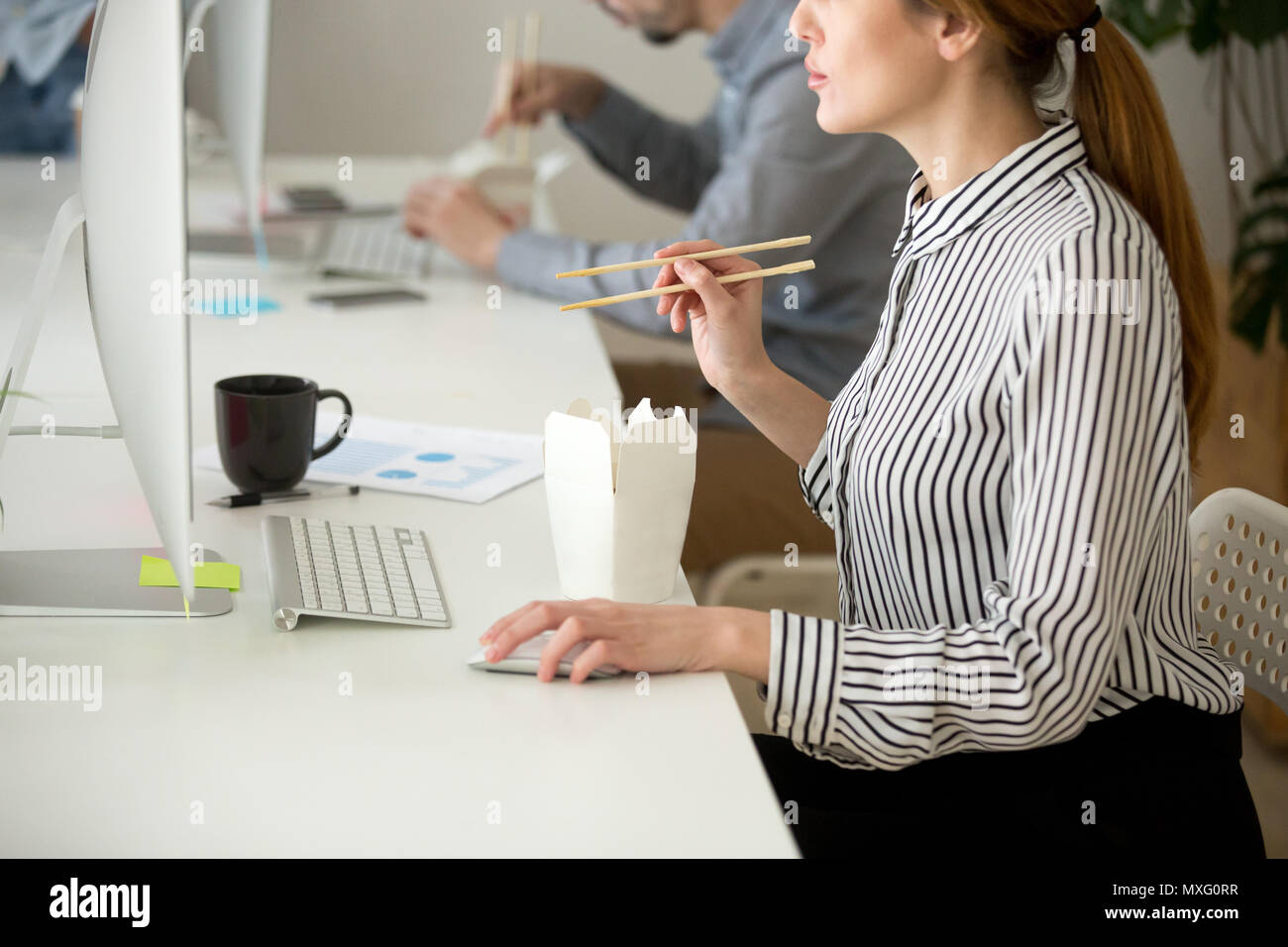 Focused female eating Asian food while working at desktop comput - Stock Image