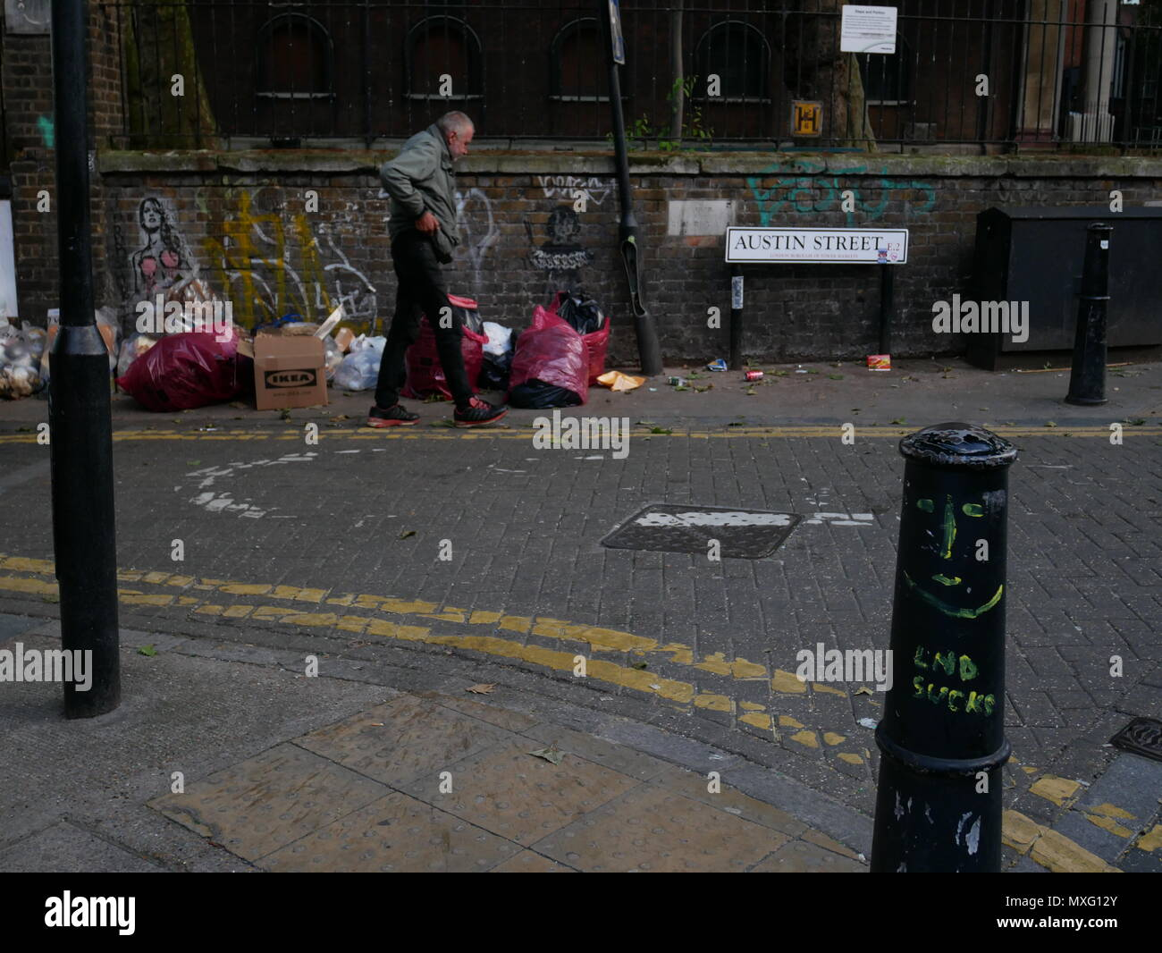 A homeless man walks past bags of rubbish outside St Leonards Church of England, Shoreditch, London. - Stock Image