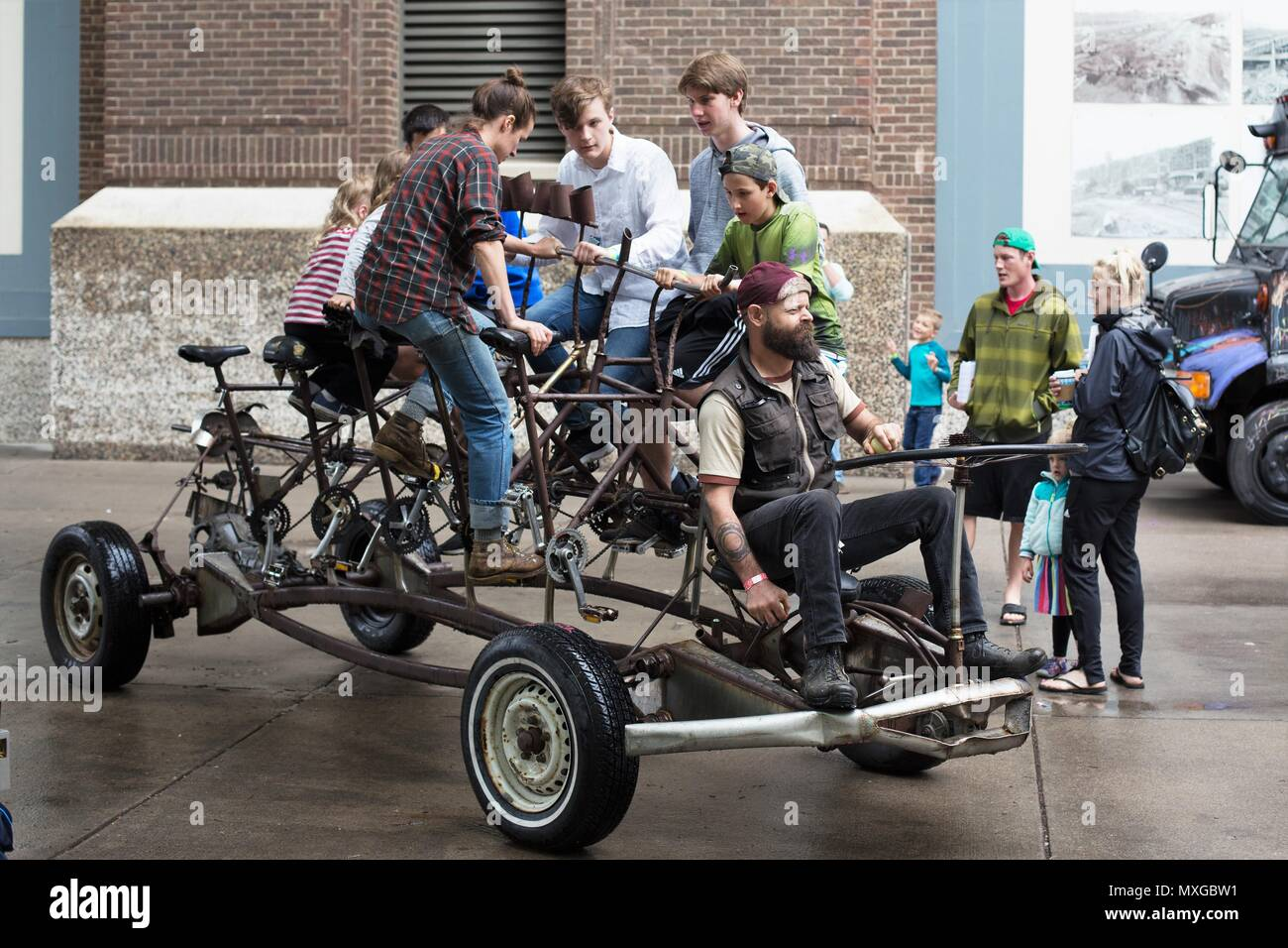 People pedaling a bike car, called the Pedal Cloud, at the