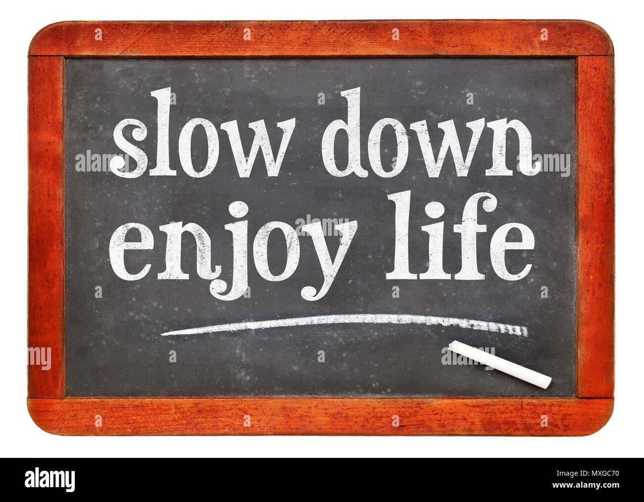 Slow down, enjoy life - white chalk text on a vintage slate blackboard Stock Photo
