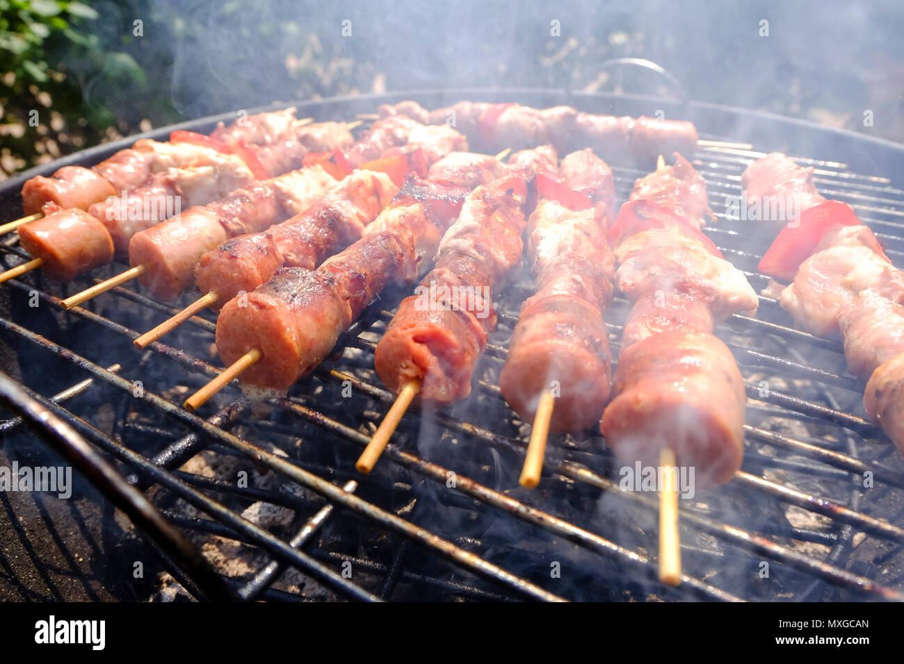 A sunny  day in the garden, starting the fire in the grill and then grilling meat skewers with friends - Stock Image