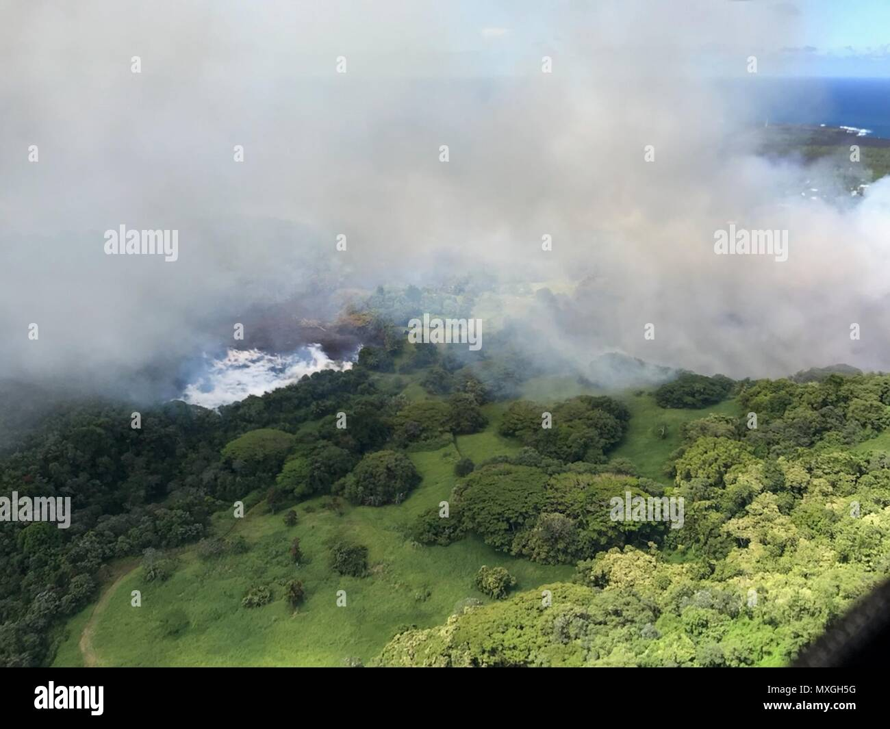 Green Lake is vaporized as lava from fissure 8 causes it to boil away sending a white plume high into the sky caused by the eruption of the Kilauea volcano June 2, 2018 in Hawaii. The recent eruption continues destroying homes, forcing evacuations and spewing lava and poison gas on the Big Island of Hawaii. - Stock Image