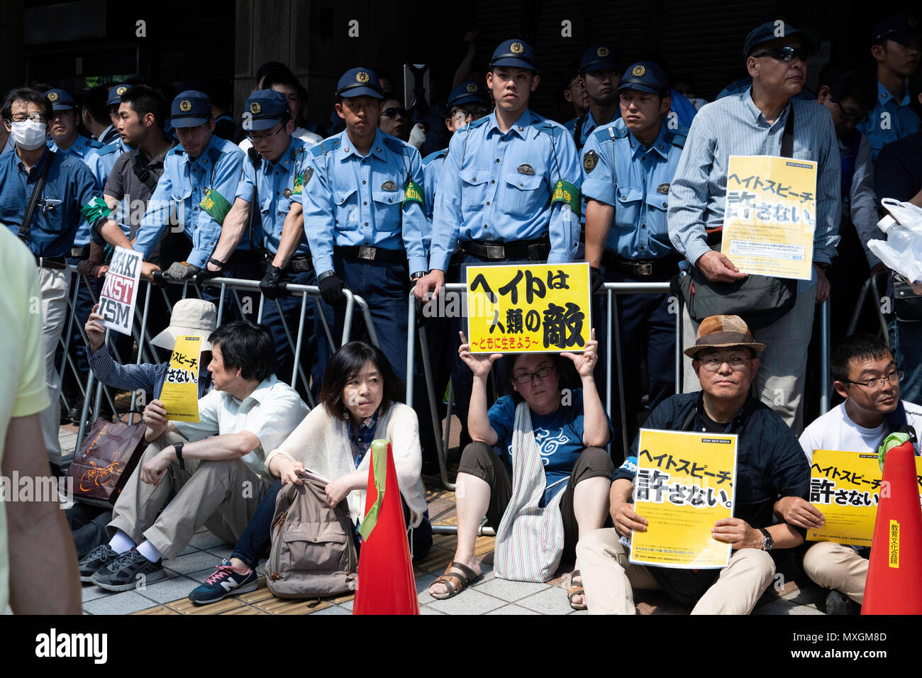 """KAWASAKI, JAPAN - JUNE 03: Protesters holding up signs, including one saying """"NO HATE & NO RACISM"""" gather in front of Educational Cultural Hall in Kawasaki, Kanagawa prefecture, Japan on June 3, 2018. The anti-racist group forcefully stop the nationalists attendees from entering the building for a planned meeting by a hate speech members in Kanto region following a scuffle with the police, nationalists and the protesters. (Photo: Richard Atrero de Guzman/Aflo) Stock Photo"""