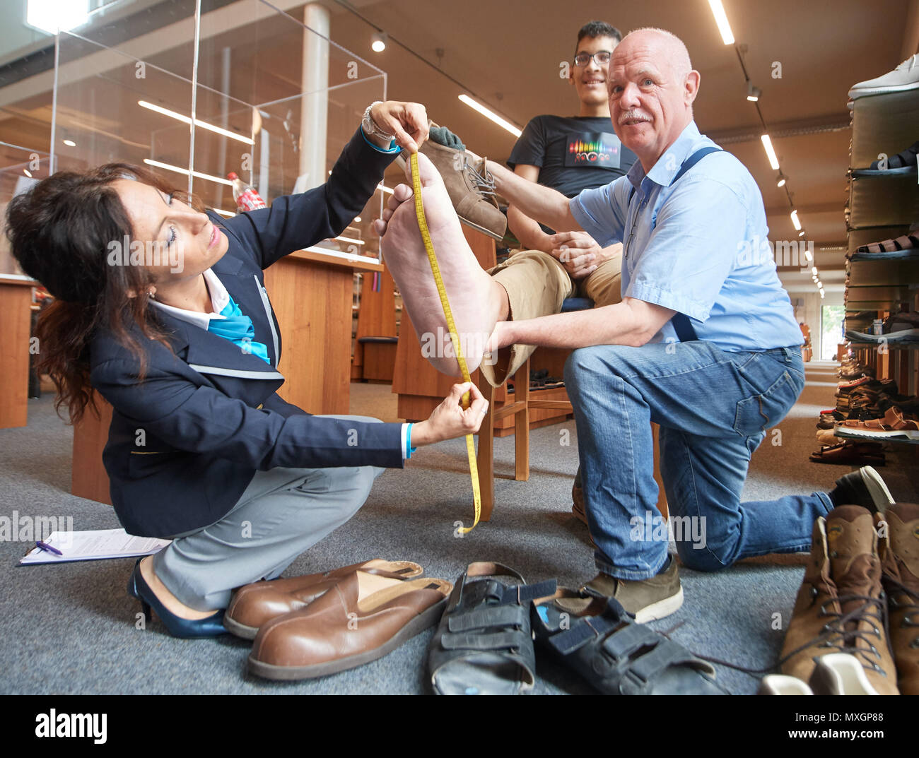 04 June 2018, Vreden, Germany: The right foot of Jeison Rodriguez, the man with the world's biggest feet, is being measured by Lucia Sinigagliesi, Judge of the Guniess World Records and Georg Wessels of the Oversized shoe making workshop 'Wessels'. The 22 year- old from Venezuela wears a size 68 and has had his shoes specially made for him by a Shoemaker from Vreden (near the Borders of Netherlands) for the past 5 years. Guiness World Records has confirmed on June 4, 2018 that his massive feet with 40.55 cm left and 40.57 cm right are still the world's biggest feet. Photo: Bernd Thissen/dpa - Stock Image