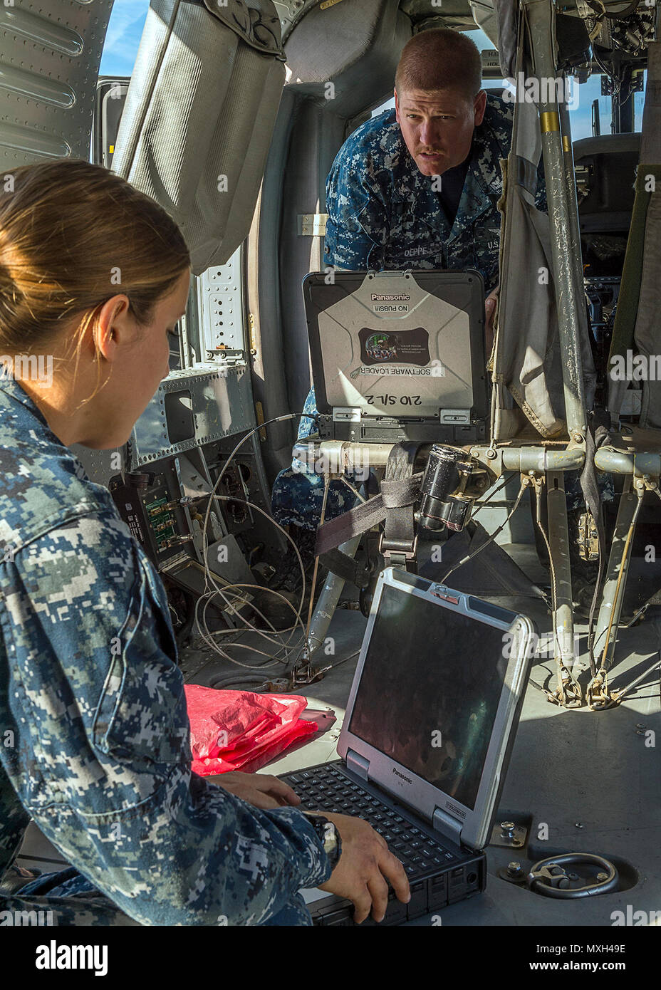 """Petty Officer 3rd Class Angela Bobst and Petty Officer 2nd Class Ryan Deppe assigned to Helicopter Sea Combat Squadron (HSC) 21 """"Blackjacks"""", review schematics on a toughbook laptop on a MH-60S Seahawk, while the helicopter is under regular maintenance check-ups on the flight line in San Diego, Nov. 4, 2016. HSC-21's mission is to provide all-weather, vertical lift, and combat-ready aircraft and crews to U.S. 7th and 5th Fleet areas of responsibility. U.S. Navy Combat Camera photo by Petty Officer 1st Class Bryan Ilyankoff - Stock Image"""