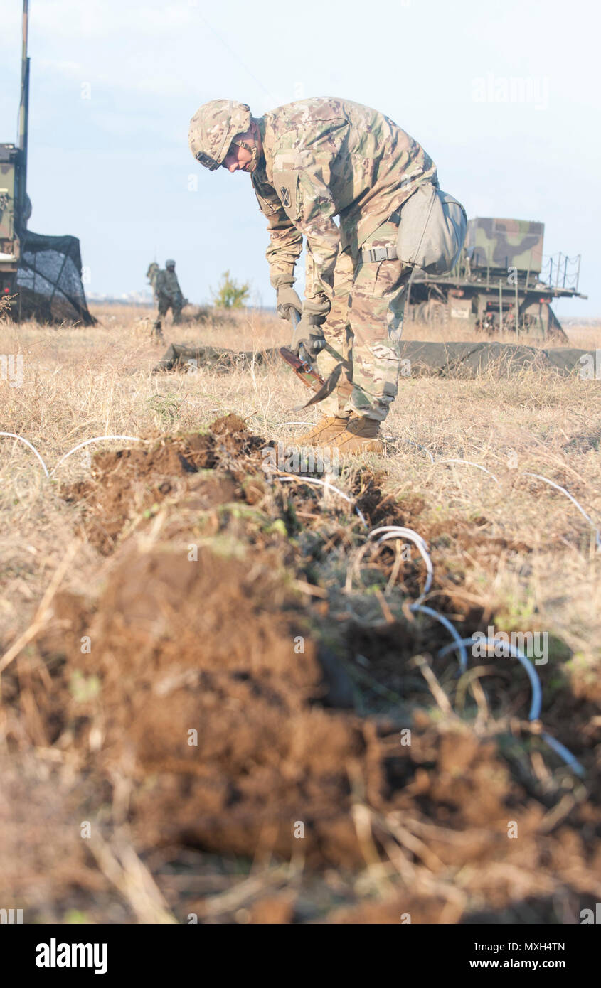 """U.S. Army Sergeant Joseph Harris, a Soldier with the 5th Battalion 7th Air Defense Artillery Regiment, digs a trench to bury cable during a """"Patriot Shock"""" exercise in Capu Midia, Romania on November 5, 2016. The weeklong exercise tests the unit's quick response deployment readiness and increases joint interoperability with """"Patriot"""" missile systems and their Romanian partners. (DoD News photo by Tech. Sgt. Brian Kimball) - Stock Image"""