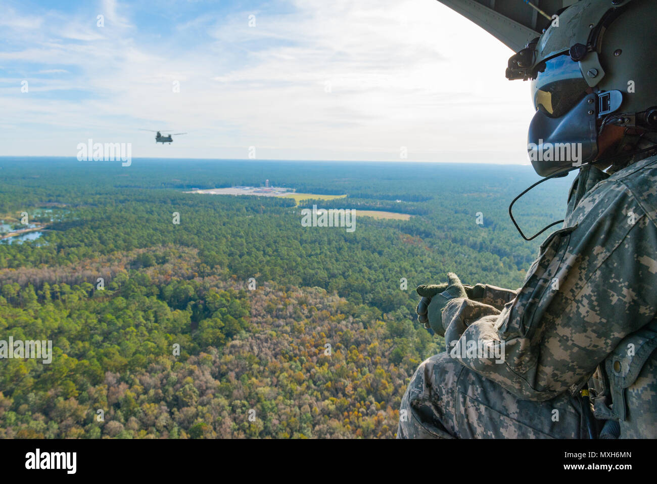 A U.S. Army Chinook crewmember assigned to the 3rd Combat Aviation Brigade observes Chinooks in flight over Fort Stewart during a slingload training mission at Hunter Army Airfield, Nov. 6, 2016. The soldiers are transporting howitzers to a training area on Fort Stewart in support of the 3rd Division Artillery. (U.S. Army photo by Lt. Col. Brian J. Fickel) - Stock Image