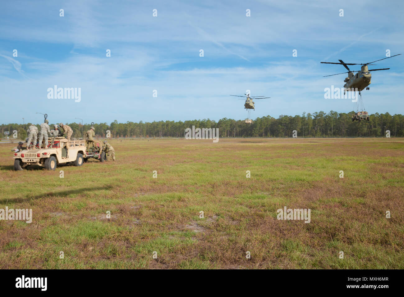 Soldiers assigned to 3rd Division Artillery prepare a Humvee and artillery piece at Fort Stewart for a slingload training mission while two Chinooks transport equipment, Nov. 6, 2016. The soldiers are transporting howitzers to a training area on Fort Stewart in support of the 3rd Division Artillery. (U.S. Army photo by Lt. Col. Brian J. Fickel) - Stock Image