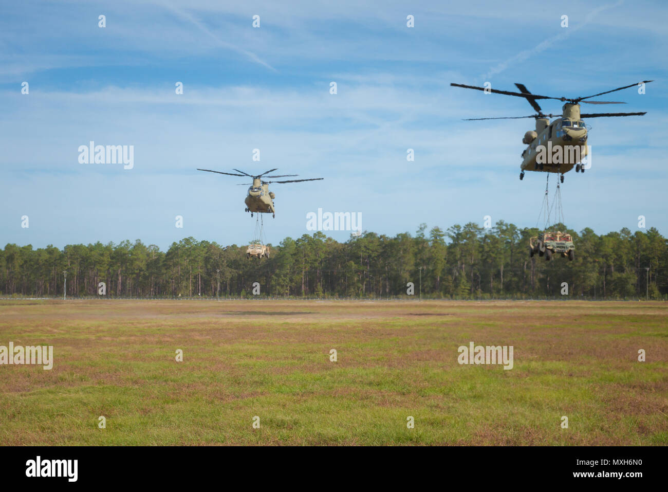Two Chinooks assigned to 3rd Combat Aviation Briade transport Humvees and artilley pieces during a slingload training mission at Fort Stewart, Nov 6, 2016. (U.S. Army photo by Lt. Col. Brian J. Fickel) - Stock Image