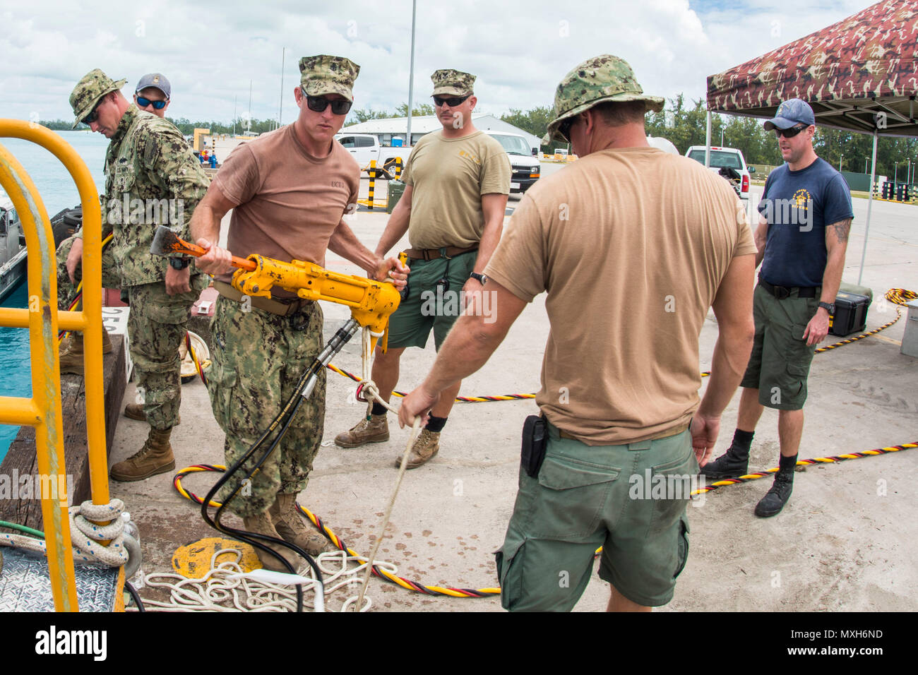Chief Petty Officer Jesse Hamblin, center, assigned to Underwater Construction Team (UCT) 2's Construction Dive Detachment Bravo, moves a hydraulic tool in Diego Garcia, Nov. 4, 2016. CDDB is performing precision underwater demolition and light salvage to remove obstructions from Diego Garcia's deep draft wharf. CDDB is on the third stop of their deployment, where they are conducting inspection, maintenance, and repair of various underwater and waterfront facilities while under Commander, Task Force (CTF) 75, the primary expeditionary task force responsible for the planning and execution of co Stock Photo