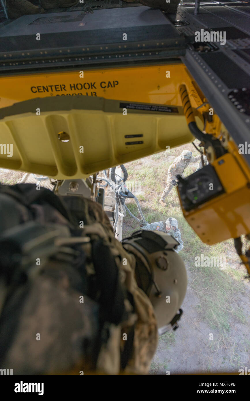 Soldiers assigned to 3rd Division Artillery hook up a Humvee and artillery piece to a Chinook from 3rd Combat Aviation Brigade on Fort Stewart, 6 Nov 2016. (U.S. Army photo by Lt. Col. Brian J. Fickel) - Stock Image