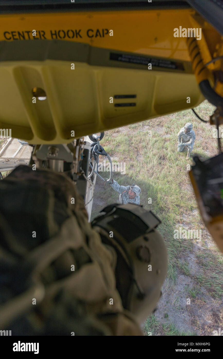 Soldiers assigned to 3rd Division Artillery hook up a Humvee and artillery piece to a Chinook from 3rd Combat Aviation Brigade on Fort Stewart, 6 Nov 2016. (U.S. Army photo by Lt. Col. Brian J. Fickel) Stock Photo