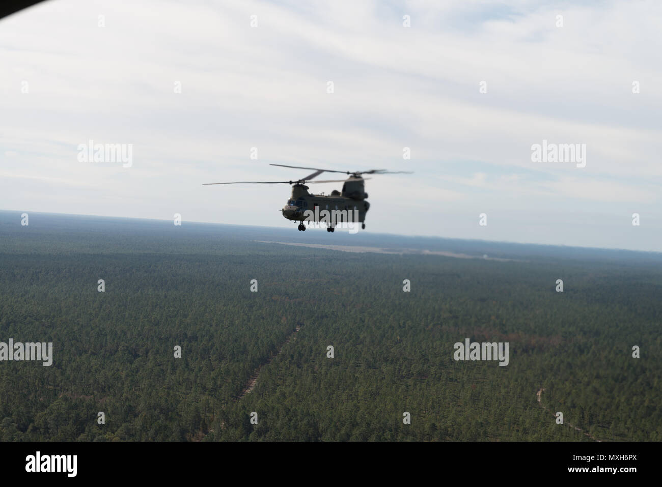 A U.S. Army Chinook maneuvers from Hunter Army Airfield to Fort Stewart during a slingload mission in support of the 3rd Division Artillery, Nov. 6, 2016. (U.S. Army photo by Lt. Col. Brian J. Fickel) - Stock Image