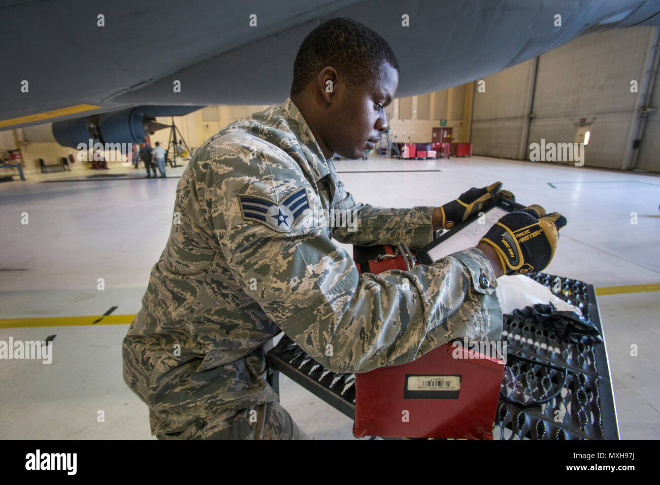 Senior Airman Andy Amakihe, KC-135R Stratotanker Crew Chief, 108th Wing, New Jersey Air National Guard, reviews a technical order prior to lowering the refueling boom for inspection at Joint Base McGuire-Dix-Lakehurst, N.J., Nov. 5, 2016. (U.S. Air National Guard photo by Master Sgt. Mark C. Olsen/Released) - Stock Image