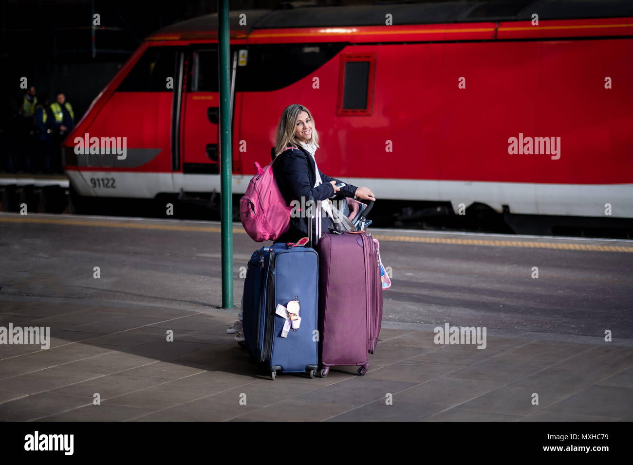 Attractive blond woman looking tired and busy with many bags and luggage at a train station with red train in the backgroud - Stock Image