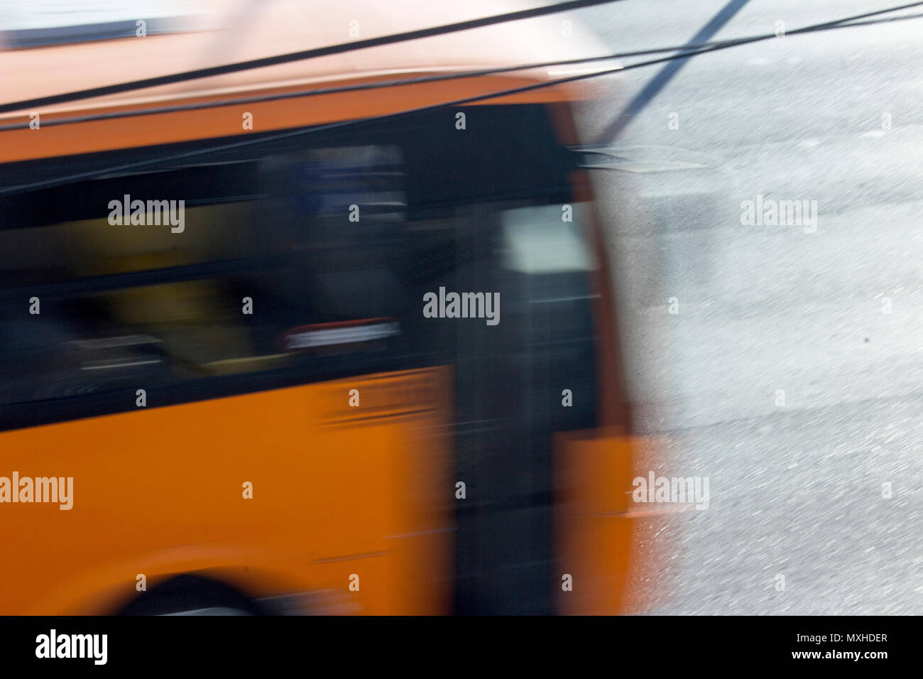 An orange public bus transits in an avenue of Monterrey, Nuevo Leon, Mexico, in the afternoon. Stock Photo