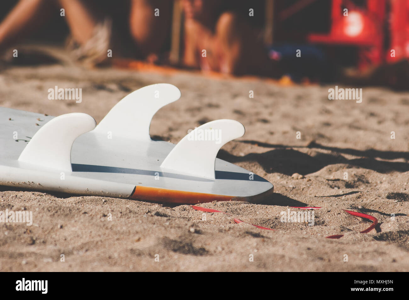Tail of a surfboard on the sand with three fin - Stock Image