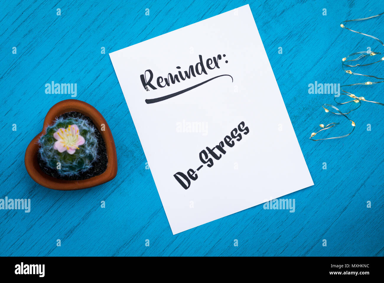 Reminder to De-Stress still life motivational concept on white paper and blue table flat lay in vintage tones - Stock Image