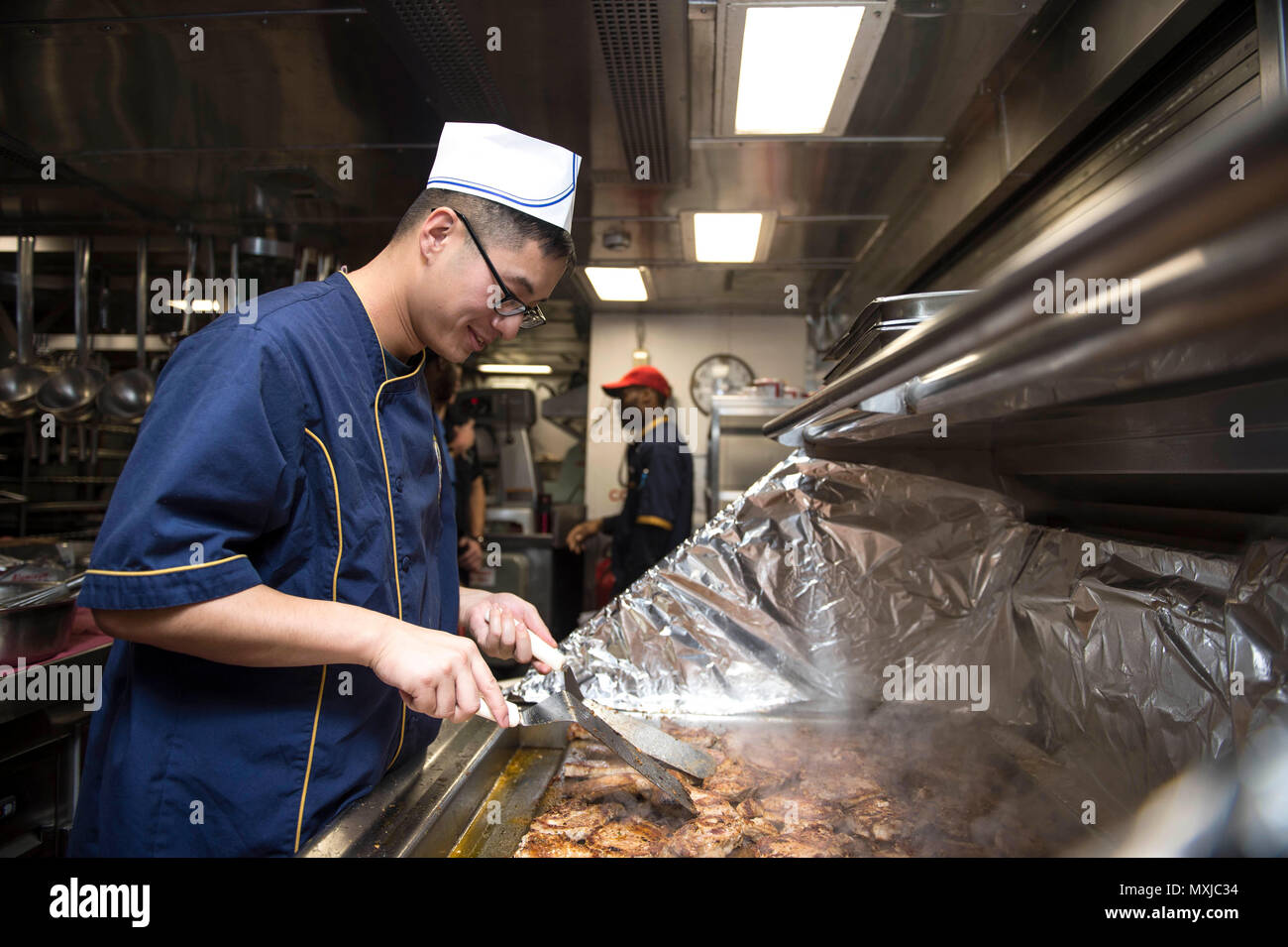 161107-N-XQ474-016 PHILIPPINE SEA (Nov. 7, 2016) Seaman Hing Leung Tsang cooks pork chops in the galley aboard the Ticonderoga-class guided-missile cruiser USS Chancellorsville (CG 62). Chancellorsville is on patrol in the Philippine Sea with Carrier Strike Group Five (CSG 5) supporting security and stability in the Indo-Asia-Pacific region. (U.S. Navy photo by Petty Officer 2nd Class Andrew Schneider/Released) - Stock Image