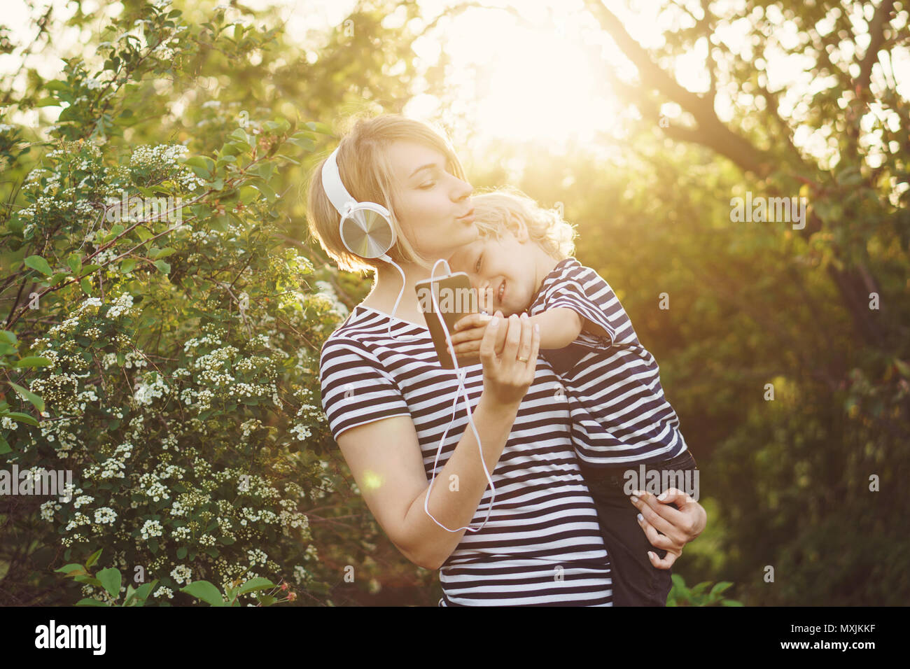 Mother and son in striped T-shirts. Woman listens to music on headphones and holds boy in her arms. He is holding cell phone and making selfie. Family - Stock Image