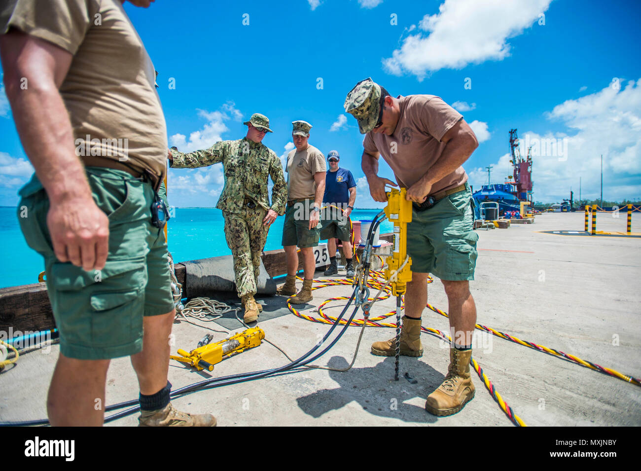 Chief Petty Officer Dan Luberto, right, assigned to Underwater Construction Team (UCT) 2's Construction Dive Detachment Bravo (CDDB), tests a hydraulic hammer drill in Diego Garcia, British Indian Ocean Territory, Nov. 7, 2016.  CDDB is performing precision underwater demolition and light salvage to remove obstructions from Diego Garcia's deep draft wharf. CDDB is on the third stop of their deployment, where they are conducting inspection, maintenance, and repair of various underwater and waterfront facilities while under Commander, Task Force (CTF) 75, the primary expeditionary task force res Stock Photo