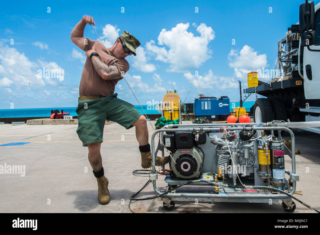 Chief Petty Officer Scott Schleisman, assigned to Underwater Construction Team (UCT) 2's Construction Dive Detachment Bravo (CDDB), starts an air compressor in Diego Garcia, British Indian Ocean Territory, Nov. 7, 2016. CDDB is performing precision underwater demolition and light salvage to remove obstructions from Diego Garcia's deep draft wharf. CDDB is on the third stop of their deployment, where they are conducting inspection, maintenance, and repair of various underwater and waterfront facilities while under Commander, Task Force (CTF) 75, the primary expeditionary task force responsible  Stock Photo