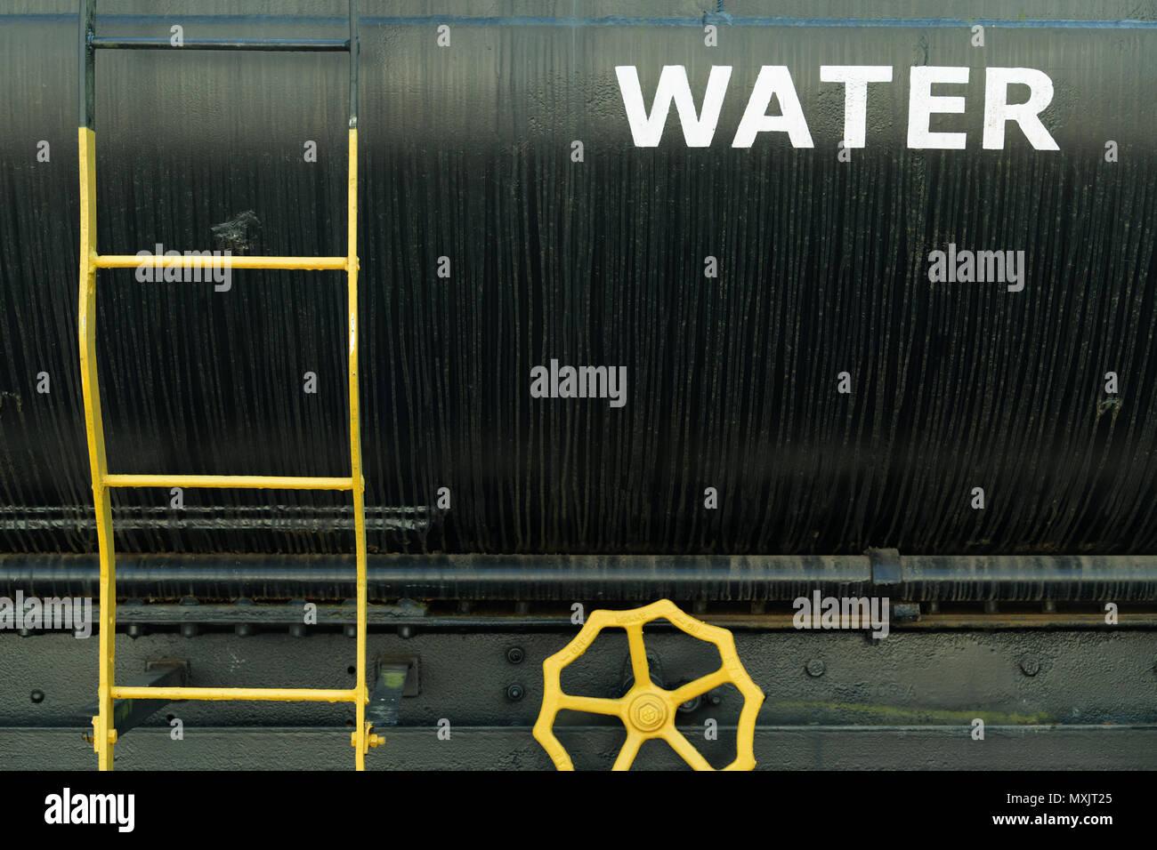 Yellow metal ladder on black bulk water tank of a railcar Stock Photo