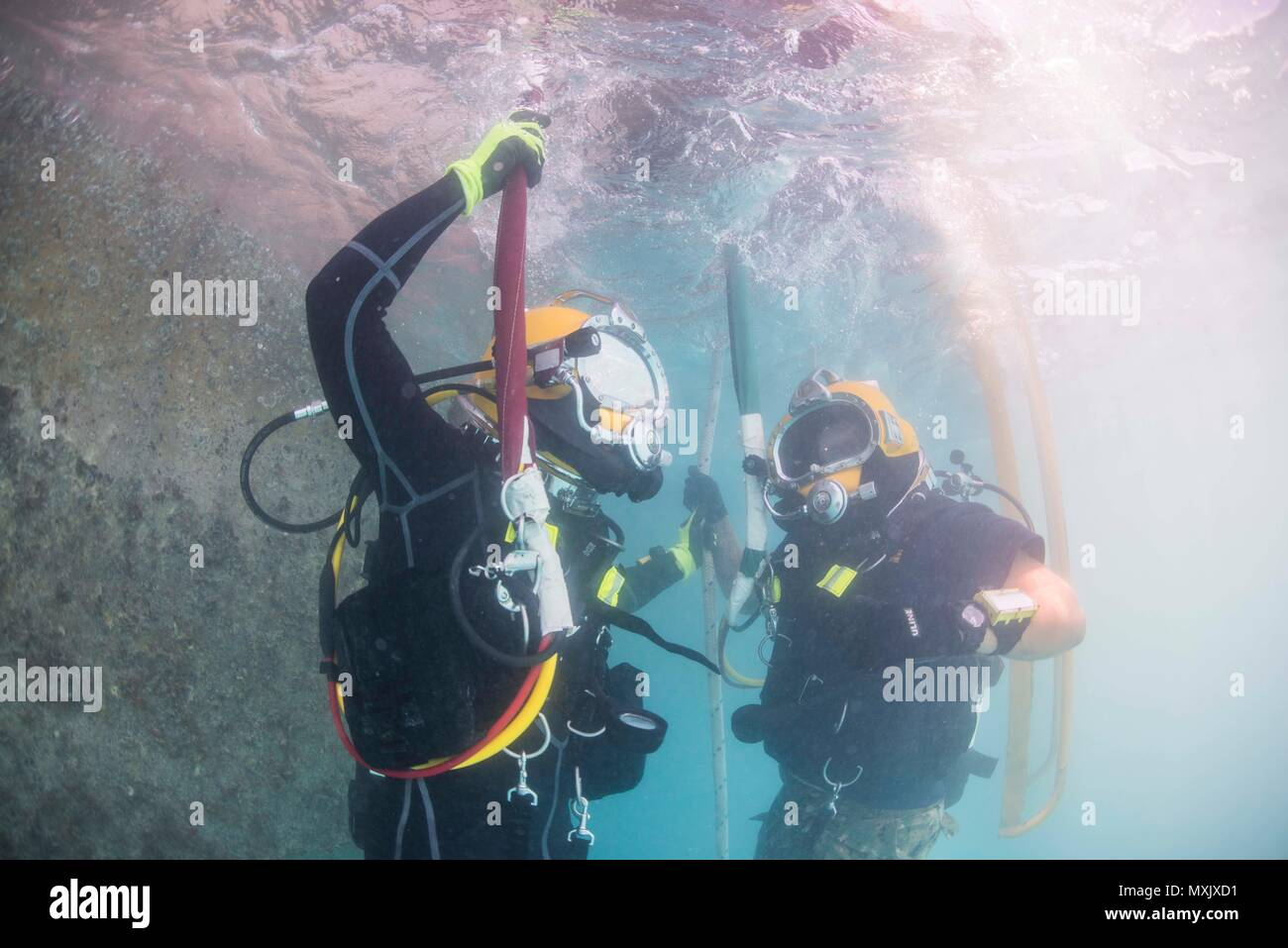 Chief Petty Officer Jesse Hamblin, left, and Petty Officer 2nd Class Aaron Brown, both assigned to Underwater Construction Team (UCT) 2's Construction Dive Detachment Bravo (CDDB), conduct diving operations in Diego Garcia, British Indian Ocean Territory, Nov. 8, 2016.  CDDB is performing precision underwater demolition and light salvage to remove obstructions from Diego Garcia's deep draft wharf. CDDB is on the third stop of their deployment, where they are conducting inspection, maintenance, and repair of various underwater and waterfront facilities while under Commander, Task Force (CTF) 75 Stock Photo
