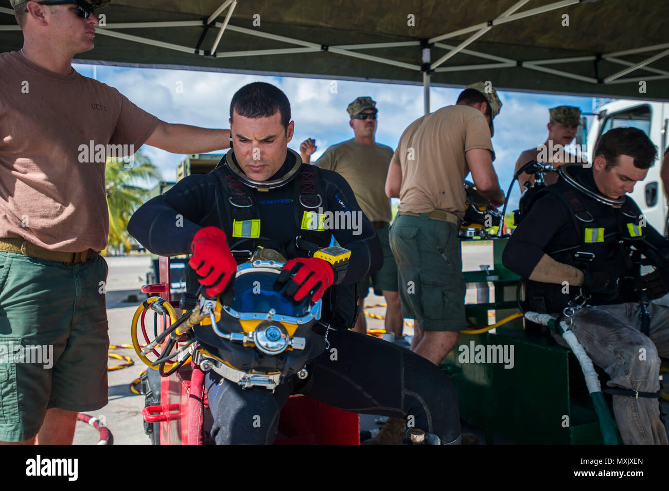 Chief Petty Officer Dan Luberto, center, assigned to Underwater Construction Team (UCT) 2's Construction Dive Detachment Bravo (CDDB), performs surface checks on his KM-37 diving helmet in Diego Garcia, British Indian Ocean Territory, Nov. 10, 2016.  CDDB is performing precision underwater demolition and light salvage to remove obstructions from Diego Garcia's deep draft wharf. CDDB is on the third stop of their deployment, where they are conducting inspection, maintenance, and repair of various underwater and waterfront facilities while under Commander, Task Force (CTF) 75, the primary expedi Stock Photo