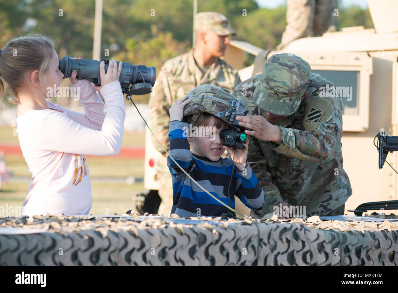 3rd Infantry Division family members takes peer through optics at a static display during Marne Week on Fort Stewart Nov. 15, 2016. Marne Week is a week of special activities for soldiers and family members in celebration of the 99th anniversary of the 3rd Infantry Division. (Photo by LTC Brian J. Fickel) Stock Photo