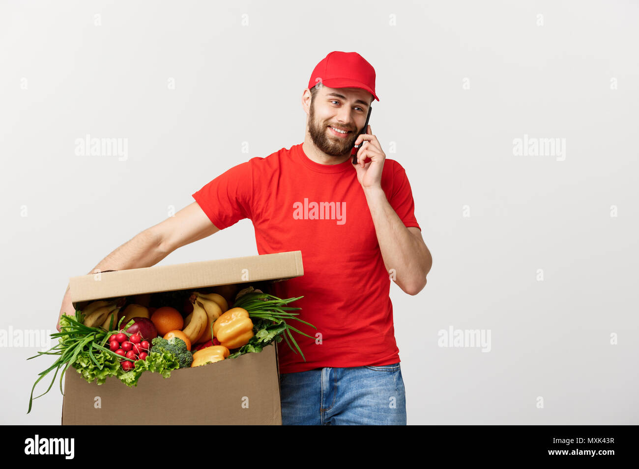 Delivery man holding paper box with food and making a call with mobile phone isolated over grey background. - Stock Image