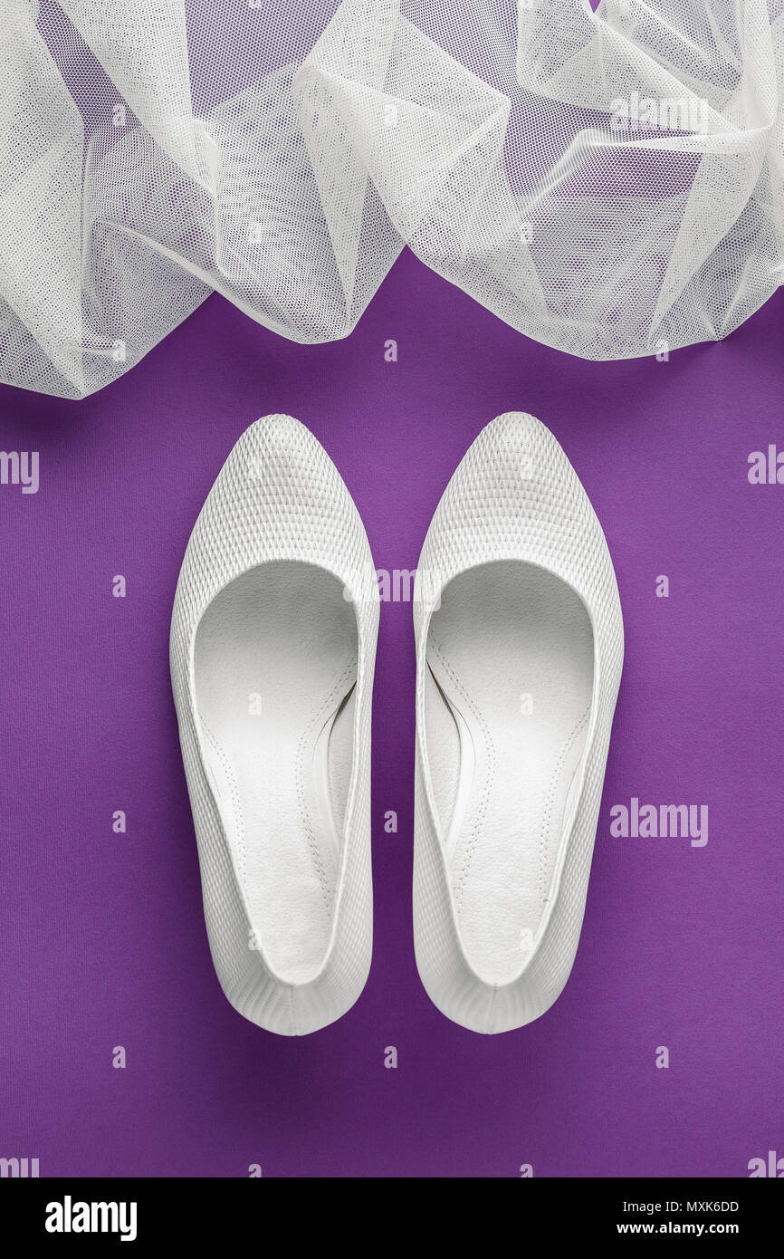 White wedding shoes with veil on purple background Stock Photo ...
