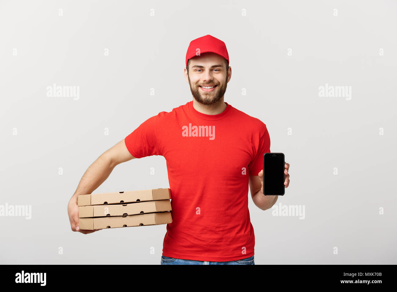 Pizza delivery man holding a mobile and pizza boxes over white background. - Stock Image