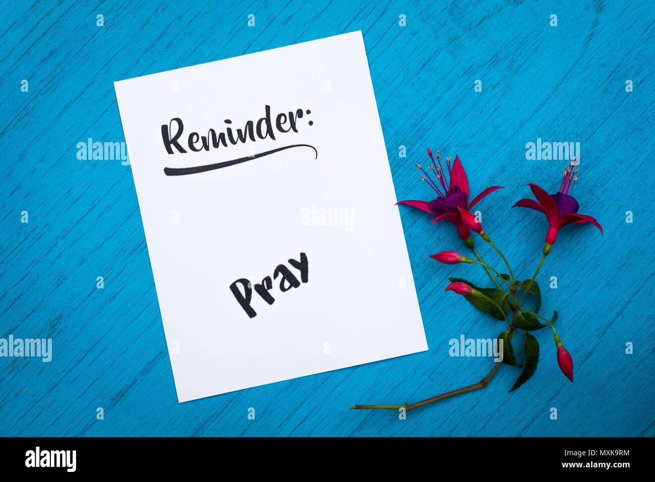 Reminder to Pray still life motivational concept on white paper and blue table flat lay in vintage tones - Stock Image